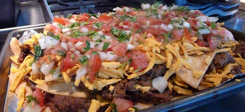 mission tortillas for vegan nachos - flour tortillas deep fried and layered with amy\'s black beans and soy taco meat and follow your heart cheese and pico de gallo