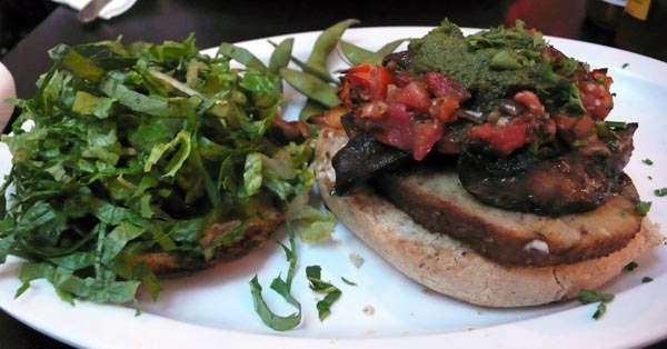 portobello &amp; sausage burger: big grilled beauties with seitan sausage, pommodoro, caramelized onions, vegan mayo, pesto and sweet roasted garlic. $10.35
