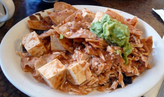 vegan chilaquiles: tofu, crisp corn tortilla chips drenched in ranchero salsa atop a bed of black beans and melted soy cheese, topped with guacamole and pico de gallo. can also be a burrito. $8.50