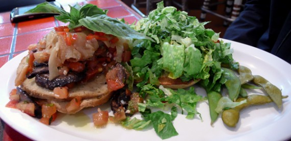 portobello & sausage burger: big grilled beauties with seitan sausage, pommodoro, caramelized onions, vegan mayo, pesto and sweet roasted garlic. $10.35
