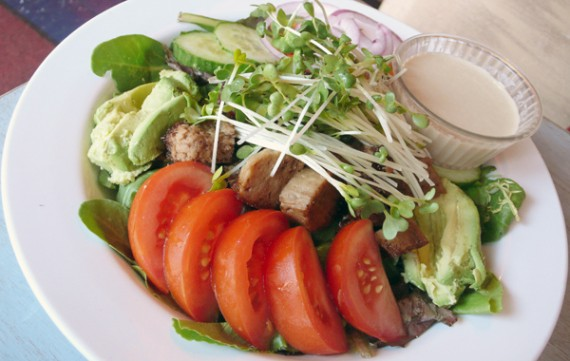Avocado &amp; Seitan Salad: Bed of mixed greens with sliced avocado, sprouts, grilled seitan, tomato and red onion. Served with choice of vinaigrette or tahini dressing. $9.95