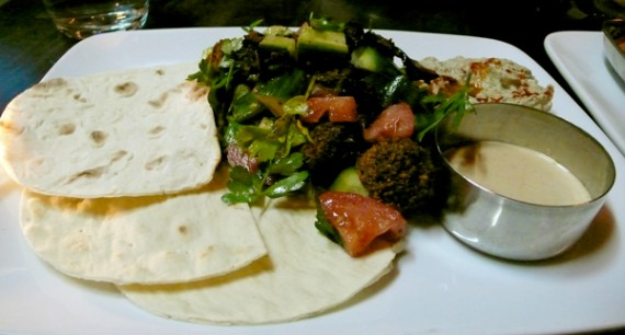 falafel salad: a salad of homemade marble sized falafel fritters tossed in crispy eggplant, tomato, cucumber, pickled radish shaved lettuce; served with thin lavash wraps, tahini hot sauce, baba ganouj and lemon oil